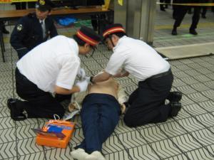 駅職員が心肺停止状態のお客さまにAEDを使用している写真