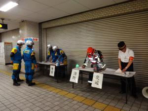 駅職員が消防士に状況報告している写真